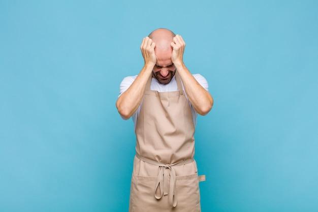 대머리 남자는 스트레스와 좌절감을 느끼고, 손을 머리에 대고, 피곤하고, 불행하고, 편두통을 느낍니다.