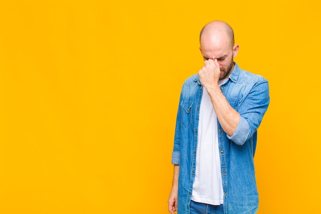 대머리 남자는 스트레스, 불행, 좌절감을 느끼고 이마를 만지고 심한 두통의 편두통을 겪습니다.