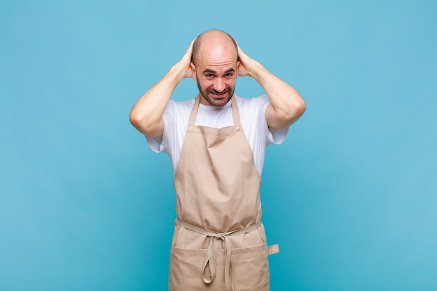 Bald man feeling stressed, worried, anxious or scared, with hands on head, panicking at mistake