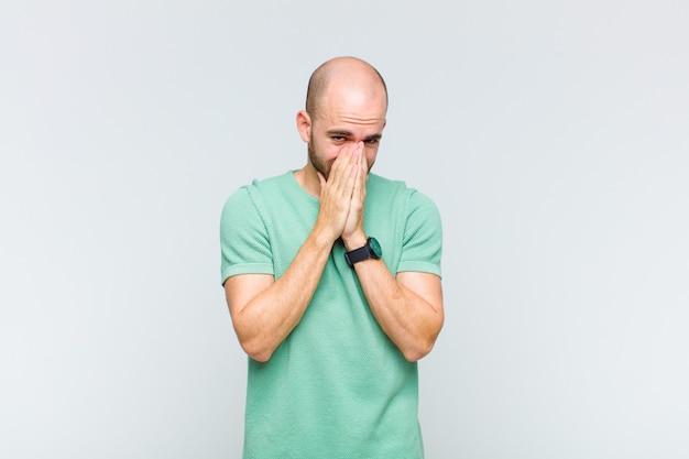 Лысый мужчина обеспокоен, полон надежд и религиозен, верно молится со сжатыми ладонями, умоляя о прощении