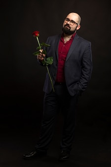 A bald man in glasses and with a beard in a suit with a red rose in his hand.