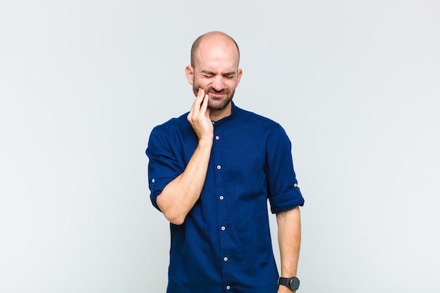 Лысый мужчина держится за щеку и страдает от болезненной зубной боли, чувствует себя больным, несчастным и несчастным, ищет стоматолога