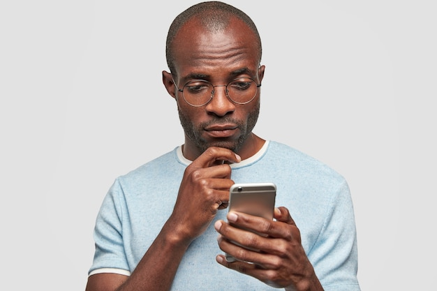 Bald man holds smart phone, looks attentively at screen of cellular, texts with friend, reads content of message
