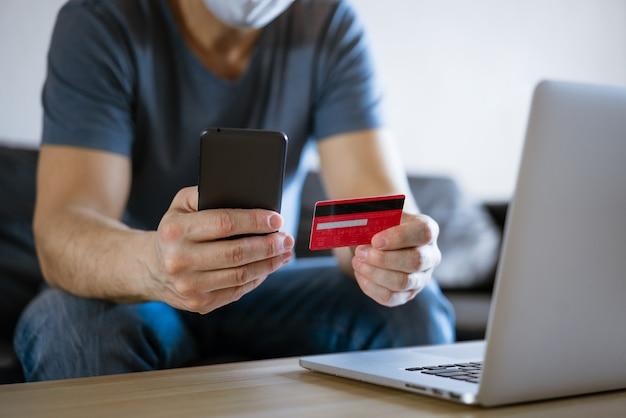 クレジットカードを持った医療マスクのハゲ男は、携帯電話を手にしたラップトップのソファに座っています。これは、オンラインストアでのオンラインショッピングの概念です。