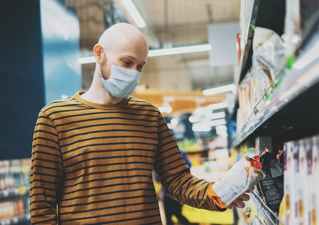 医療用フェイスマスクのハゲ男がスーパーマーケットで製品を選ぶ、コロナウイルス検疫の概念