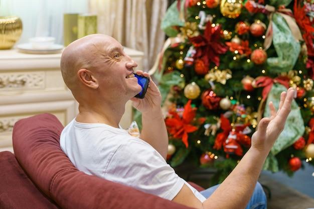 흰색 티셔츠를 입은 대머리 남자가 소파에 앉아 크리스마스 분위기를 배경으로 전화 통화를 하고 있습니다.