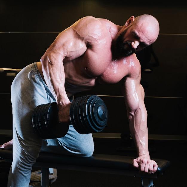Bald man lifting heavy dumbbell