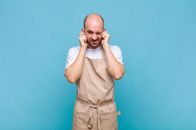 怒り、ストレス、イライラを感じ、耳をつんざくような音、音、大音量の音楽で両耳を覆っている白頭ワシの男