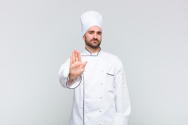 Лысый мужчина выглядит серьезным, строгим, недовольным и злым, показывая открытую ладонь, делая стоп-жест