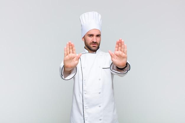 Лысый мужчина выглядит серьезным, несчастным, злым и недовольным, запрещает входить или говорит стоп с обеими открытыми ладонями