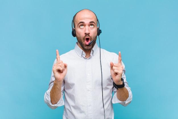 ショックを受け、驚いて、口を開けて、スペースをコピーするために両手で上向きに見える白頭ワシの男