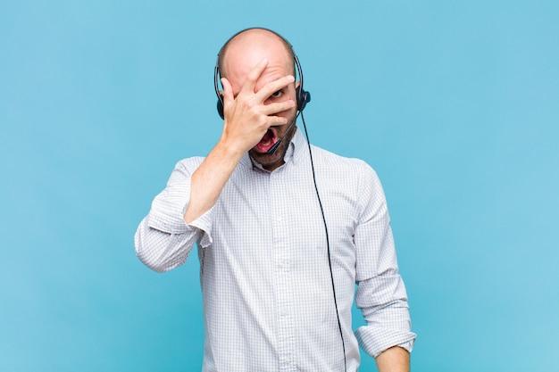 Лысый мужчина выглядит потрясенным, напуганным или испуганным, закрывает лицо рукой и смотрит между пальцами
