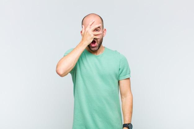 Лысый мужчина выглядит потрясенным, напуганным или напуганным, закрывает лицо рукой и смотрит между пальцами