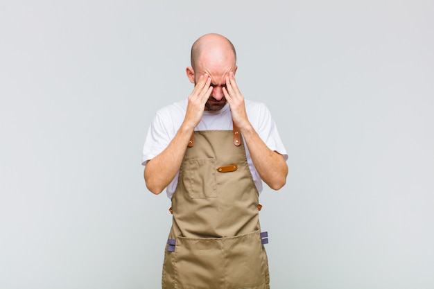 Bald man looking stressed and frustrated, working under pressure with a headache and troubled with problems