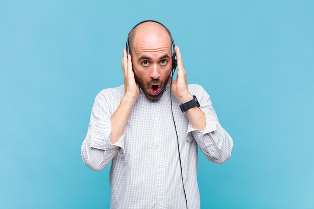 不快なショックを受けたり、怖がったり、心配したり、口を大きく開いて両耳を手で覆っている白頭ワシの男