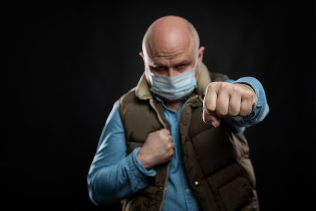 Bald man in a medical mask in a fighting stance. a blow to the disease. self-isolation during the coronavirus pandemic.