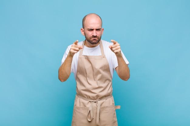 두 손가락과 화난 표정으로 앞을 향한 대머리 남자가 의무를 다하라고 말합니다.