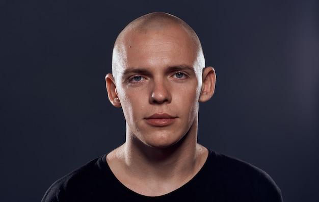 A bald man posing stoic