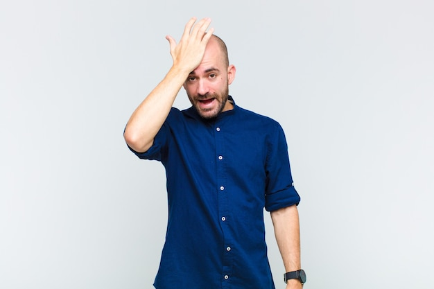 Bald man raising palm to forehead thinking oops, after making a stupid mistake or remembering, feeling dumb
