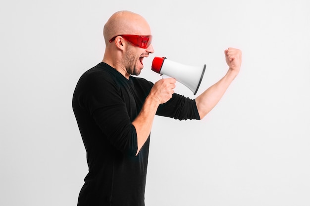 Bald man in red sunglasses shouting in loudspeaker against white wall