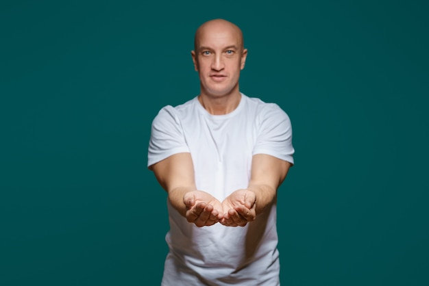 The bald man smiles and holds his hands in front of him, palms up