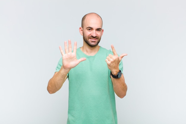 Bald man smiling and looking friendly, showing number seven or seventh with hand forward, counting down