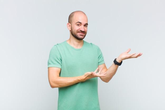 자랑스럽고 자신있게 웃고, 행복하고 만족스럽고 복사 공간에 대한 개념을 보여주는 대머리 남자