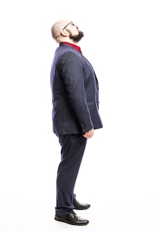 A bald man in a suit looks up. side view. full height. isolated on a white wall. vertical.