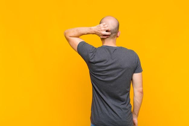 Лысый мужчина думает или сомневается, почесывает голову, чувствует недоумение и замешательство, вид сзади или сзади