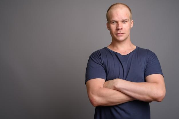 Лысый мужчина в синей рубашке у серой стены