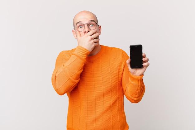 スマートフォンを持ったハゲ男が、ショックを受けた驚きの表情で口を手で覆い、秘密を守るか、おっと