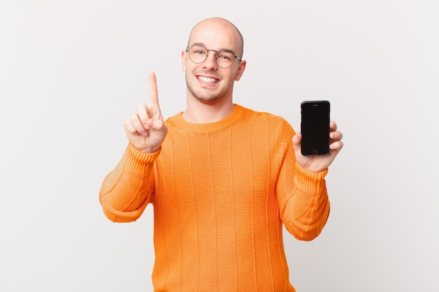 Лысый мужчина со смартфоном улыбается и выглядит дружелюбно, показывая номер один или первый с рукой форва