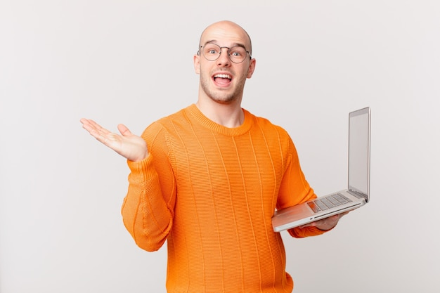 Bald man with computer feeling happy, excited, surprised or shocked, smiling and astonished at something unbelievable