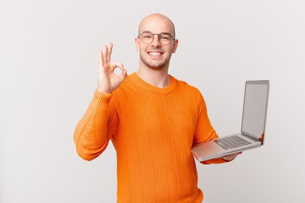 Лысый мужчина с компьютером чувствует себя счастливым, расслабленным и довольным, демонстрирует одобрение жестом ок, улыбается