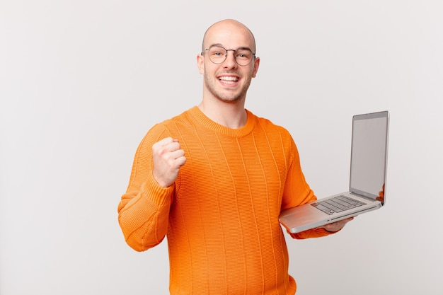 Bald man with computer feeling shocked, excited and happy, laughing and celebrating success, saying wow!