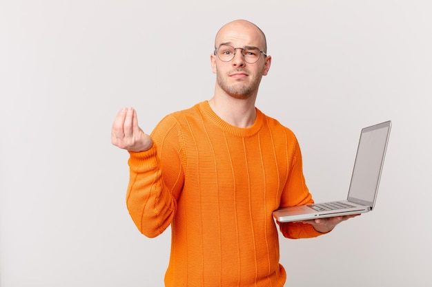 Bald man with computer making capice or money gesture, telling you to pay your debts!