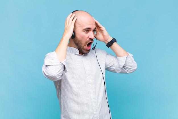 Лысый мужчина с открытым ртом, испуганный и шокированный из-за ужасной ошибки, поднимает руки к голове
