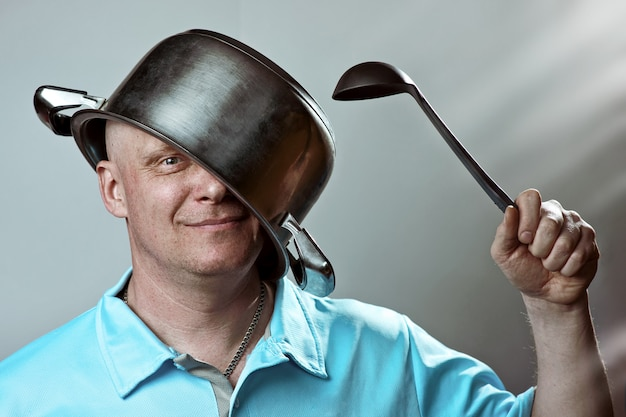 Bald man with a pot on his head and a ladle in his hand