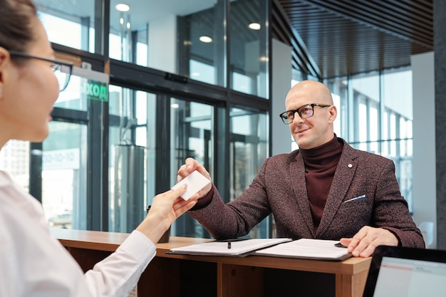 Bald mature businessman in eyeglasses and formalwear taking card from hand of receptionist after filling in form