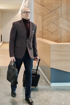 Лысый зрелый бизнесмен с сумочкой тянет чемодан во время движения по стойке регистрации в холле отеля