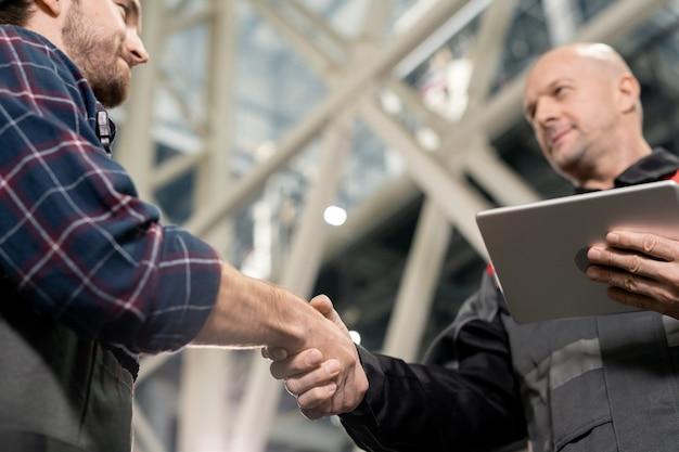Лысый зрелый бригадир с цифровым планшетом приветствует своего молодого подчиненного рукопожатием перед встречей на складе или в заводской среде