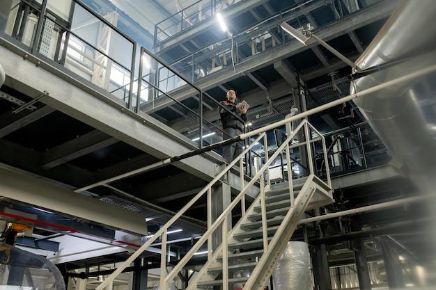 Лысый зрелый прораб с цифровым планшетом, работающий с техническими данными на современном большом заводе по переработке полимеров перед лестницей