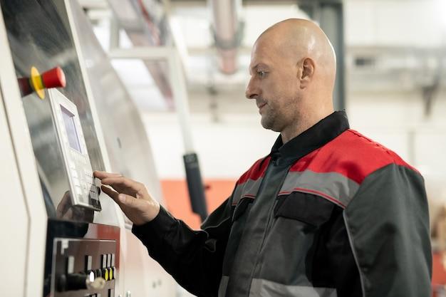 Лысый зрелый рабочий современного крупного завода по переработке полимеров нажимает кнопку на панели управления во время перезагрузки промышленного оборудования