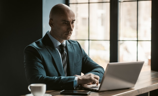 Bald middle aged businessman in business suite working on laptop next to open windows in modern office