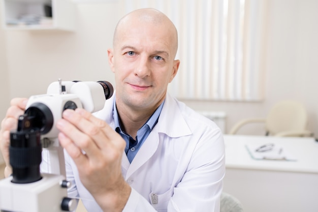Лысый глазной врач средних лет сидит с офтальмологическим оборудованием