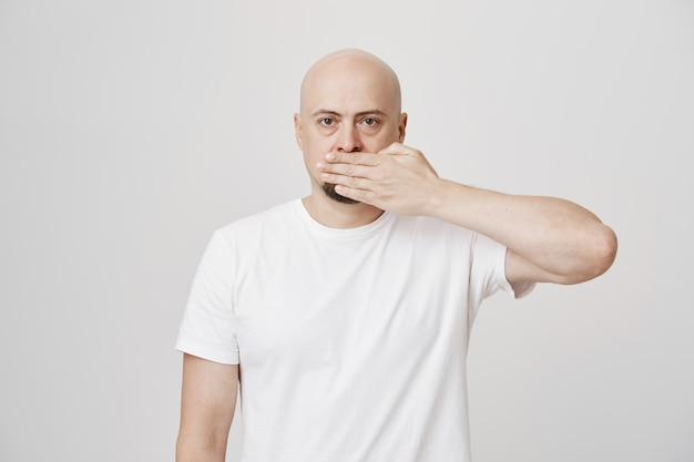 Bald middle-aged man shut mouth with palm