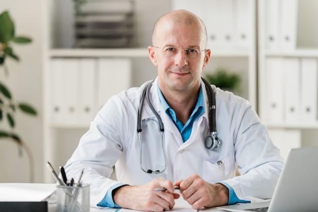 診療所や病院の机に座って彼の仕事を行うペンでハゲ専門の医者