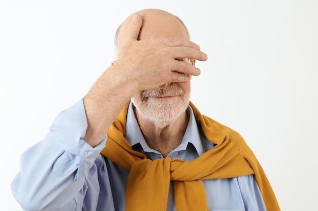 エレガントなフォーマルな服を着たハゲの年配の男性が、涙を隠そうとして、彼の目に手をつないで孤立したポーズをとっています。恥ずかしそうな年配の男性が顔の手のひらをジェスチャーします。ボディランゲージ