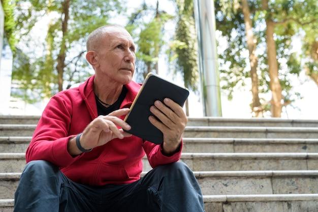 階段に座っている間デジタルタブレットを考えて保持しているハゲの年配の男性