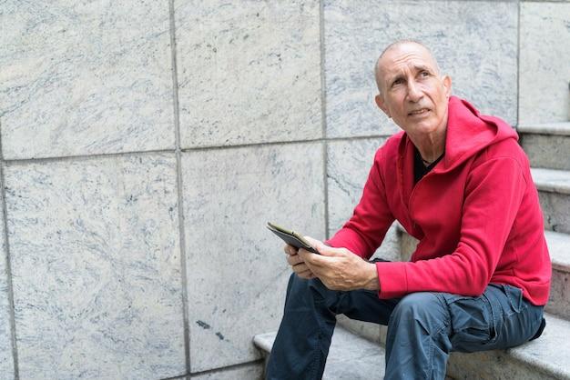デジタルタブレットを持って考えて見上げる禿げた年配の男性